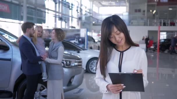 auto prodejní centrum, portrét usměvavý manažer asijské ženy na pozadí šťastní klienti pár s dítětem dívka majitelů koupil automobil v autosalonu