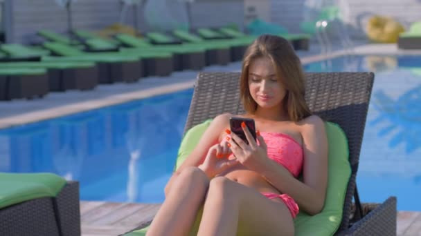 üdülőhely nyaralás, gyönyörű fiatal lány fürdőruhában pihenő közel kék medence napozóágyon belenéz telefon egy drága üdülőhely a nyári szünetben