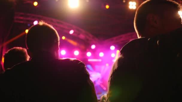 dav lidí skákat a potřást hlavami na koncertě živé hudby v jasném osvětlení reflektorů