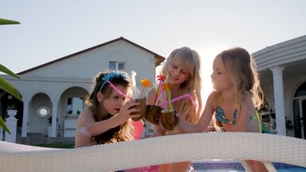 boldog gyermekkort, elkényeztetett gyerekek színes koktélokkal felfújható matracon, fürdőruhás kislányok szórakozzanak a villa közelében