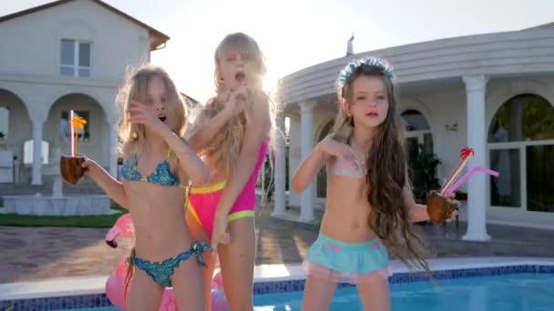 Junggesellenabschied, verwöhnte Kinder tanzen am Pool und in der Villa, Kinderpromis im Sommerurlaub, reiche Kinder mit Cocktails