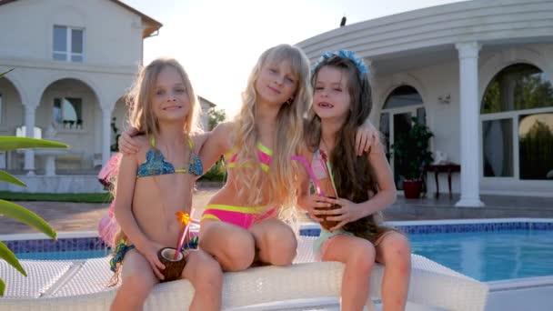 élet elkényeztetett gyerekek, gazdag gyerekek medence közelében pózol kamera, gyerekek hírességek a nyári vakáció, gyerekek party koktélokkal
