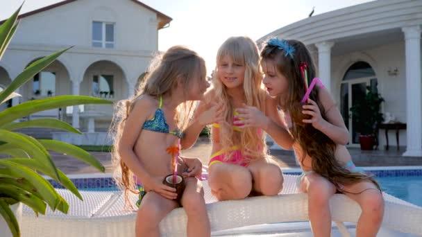 kis pletykák, gazdag gyerekek medence közelében beszélni lányos titkok, gyerekek hírességek a nyári vakáció, gyerekek party