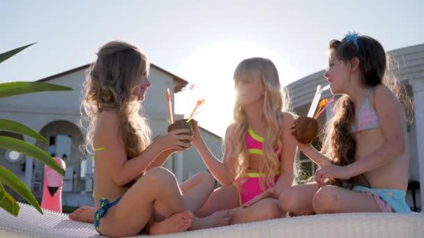 gazdag gyerekek napágyon kókuszkoktéllal a kezükben szabadban, boldog gyermekkort, elkényeztetett gyerekek színes koktélokkal