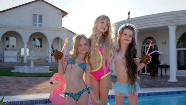 spoiled children posing on camera near pool and villa, kids celebrities in swimsuit on summer vacation, rich childs