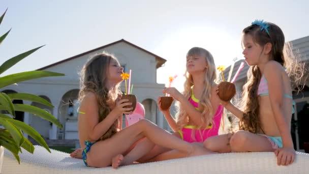 elkényeztetett gyerekek színes koktélokkal a napozóágyon, fürdőruhás kislányok szórakoznak a villa közelében háttérvilágításban, gazdag gyerekek