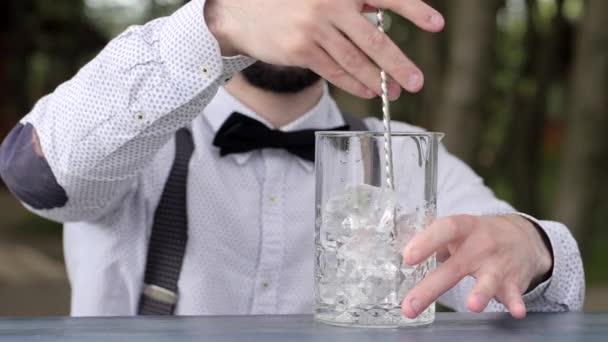 Barmann rührt Eisbar-Löffel auf Theke, Glas mit Eis in Nahaufnahme, Barkeeper macht Kühlgetränk an die frische Luft, Arbeit an der Bar