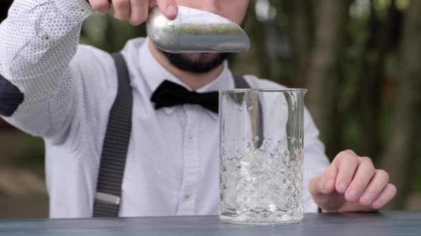 bartender at bar table put clear ice cubes in glass, barman put ice into glass in fresh air, bar worker prepares alcoholic beverage, event Service,