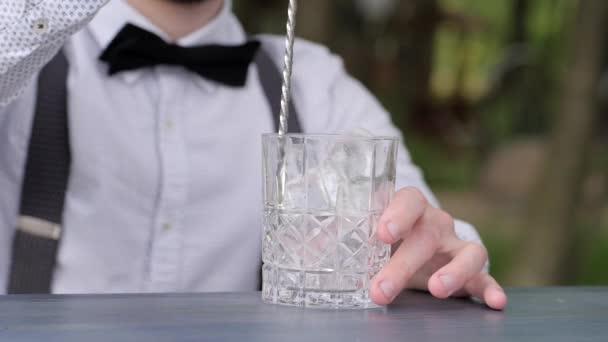 Glas mit Eis auf der Theke, Barmann rührt Eisbar Löffel in Nahaufnahme, Barkeeper macht Kühlgetränk an die frische Luft, Cocktailparty