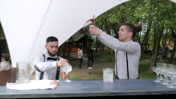 barmen show outdoors, two barkeeper mix in shaker cocktail, bar workers prepare drinks in mixing glass with filter