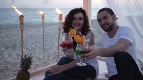 friends with cocktail in hands on beach an exotic vacation, at bungalow, romantic trip, background tropical fruits, Fire in burning torches,