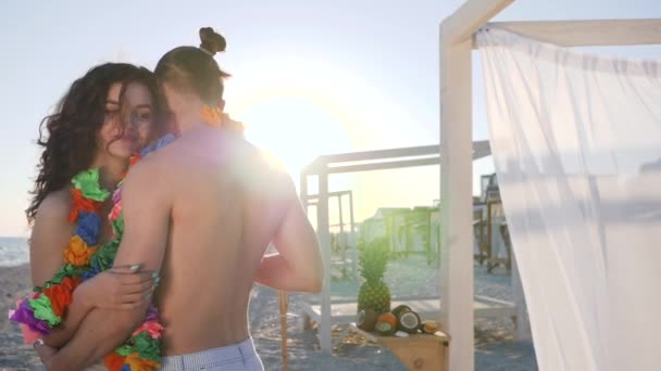 romantic atmosphere on shore of tropical island, suns rays, slow dance in love couple at exotic resort, beach party, guy gives girl hand