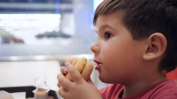 Disobedient child bites hamburger and plays with it, Beautiful baby eating, Hamburger and French fries for snack for son,
