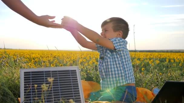 Kind trinkt Wasser auf Hintergrundfeld mit Sonnenblumen, Hand der Eltern gibt Sohn Glas im Freien, Kind sitzt in der Nähe von Solarbatterie