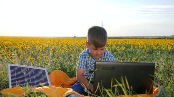 Öko, Youngster zeigt Zeichen Genehmigung in der Nähe von Solarzellen, Junge sieht in Computer mit Ladegerät im Freien, zeitgenössisches Kind