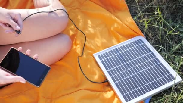 energy-generating technology, close up, hands girl connects from solar panel to mobile phone outside
