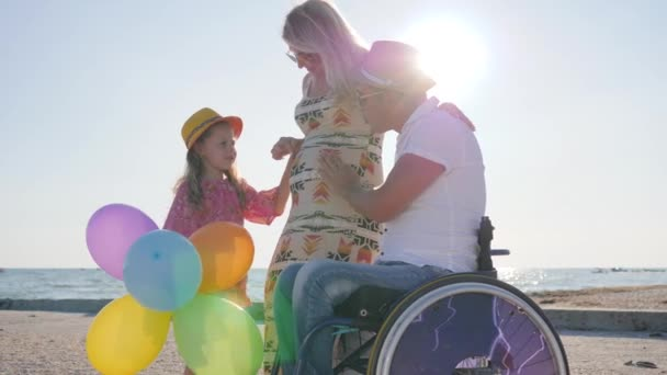 happy mother with big belly communicates with daughter and husband on wheelchair, pregnancy, disabled man