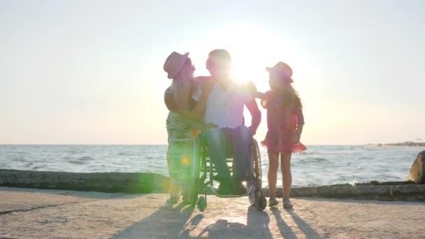 fröhliche Familie am Meer, Mann im Rollstuhl mit kleinem Mädchen und schwangere Frau im Freien, Invalide mit Frau
