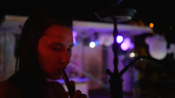 sexy young woman smoke a hookah on party in blue lights, beautiful female inhales taste of tobacco at night party