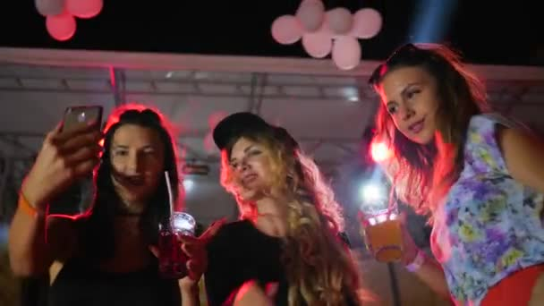 young women Make pictures on phone at disco club, self photo with bright drink at nightclub, sexy women dancing