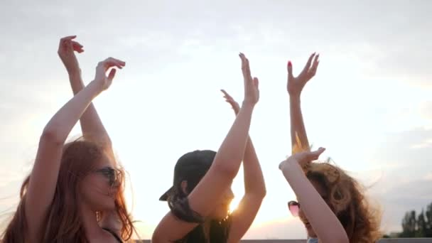 company of friends at background sundown in summer, happy three female dancing on sunset on beach