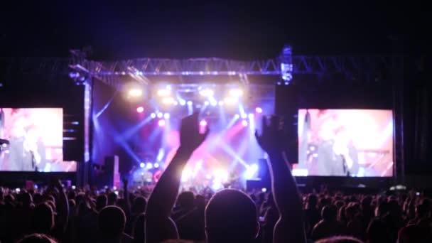 közönség integetett karját koncert vagy party, világít jelenet színes megvilágítás az éjszakai rock fesztivál