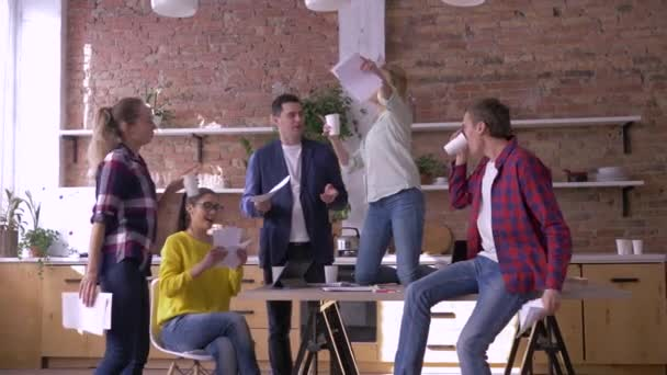 office party, crazy creative team of workers men and women having fun while job in kitchen in office and throwing documents into air