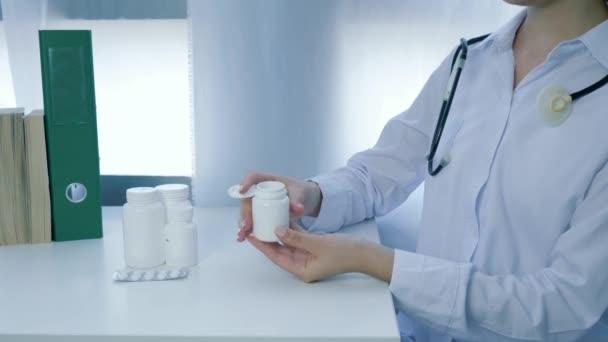 nutriční doplňky, lékař dietik ruce otevře sklenici vitamínů a nalije žluté kulaté pilulky do dlaně na bílém stole