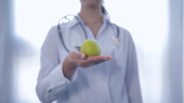 profesionální dietetolog se zeleným jablkem v ruce dává do fotoaparátu poradenství zdravé stravy pro wellness, na bílém pozadí