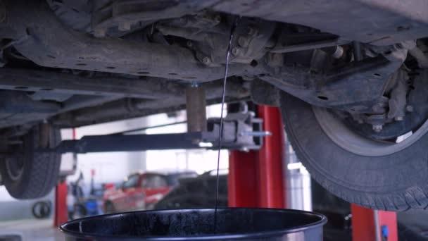 automobilový olej vtéká do kbelíku ze zdviže na čerpací stanici