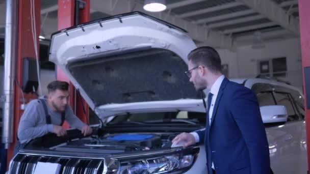 Profesionální údržba automobilů, technik je oprava vozidla s otevřenou kapotou a majitel ukazuje pozitivní gesto na čerpací stanici
