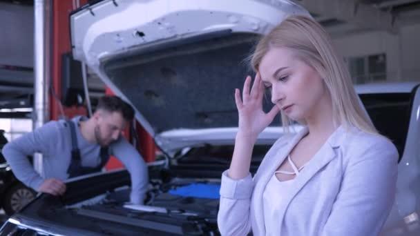 szomorú ügyfél nő ideges a törött autó nyitott motorháztető, hogy javítják a szerelő a benzinkút