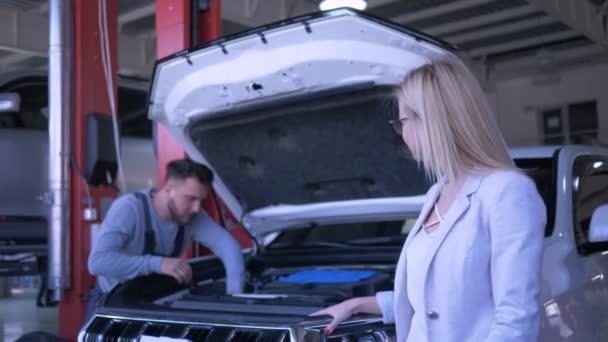 čerpací stanice, portrét šťastné paní majitelky spotřebitelského vozu při pracovním procesu mechanik opravuje vozidlo s otevřenou kapotou