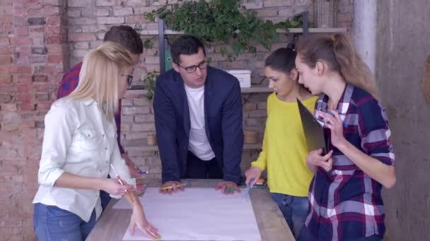 Erfolgreiches Arbeitsteam in modernem Büro, junger Chef und Mitarbeiter diskutieren über Entwicklungsprojekt neuer Geschäftsideen auf großem Zeichenpapier