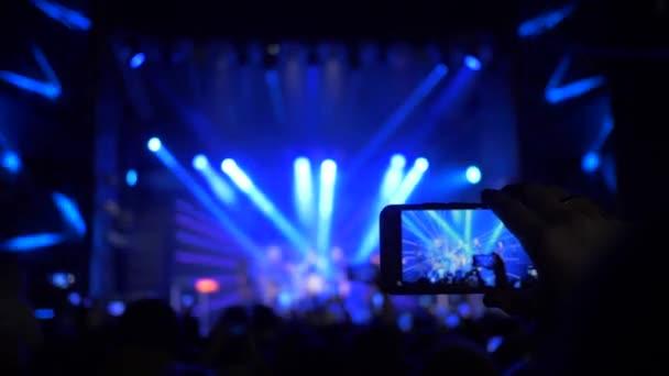 karok rajongók okostelefonok, hogy fotó és videó felvétel rock koncert színpadi reflektorfényben éjszaka
