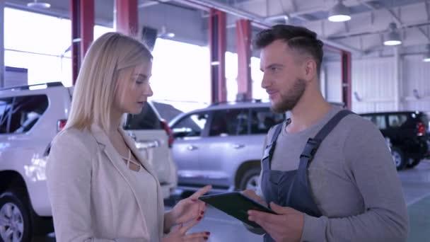 Auto business, majitel dáma a technik chlap mluví o údržbě auta na čerpací stanici