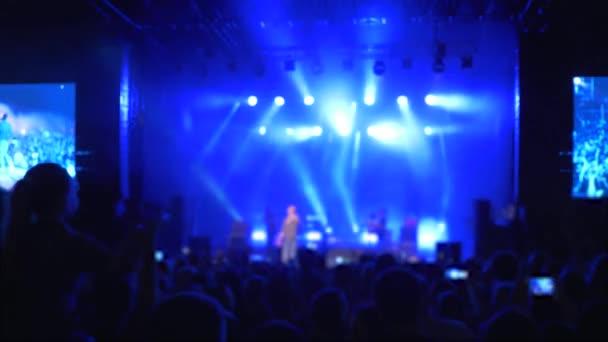 koncertní party, spousta obdivovatelů v nesoustředěném těšit živé hudební festival před jasně osvětleným jevištěm a tleskat ruce