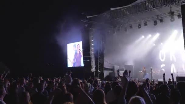 koncert party, tömeg csodálók ugrik, és integet kezét rock élő zenei esemény ellen fényes jelenet nagy képernyők éjjel