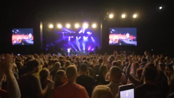 rock fesztivál, sokan élvezik és tapsolnak élő zenei koncert ellen fényes színpadon nagy képernyők éjjel