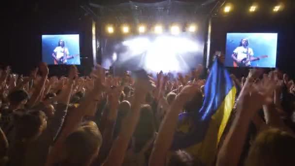 rock party, tömeg csodálók integetett kezét élő zenei koncert ellen fényes világítás színpadon nagy képernyők éjjel a sötétben