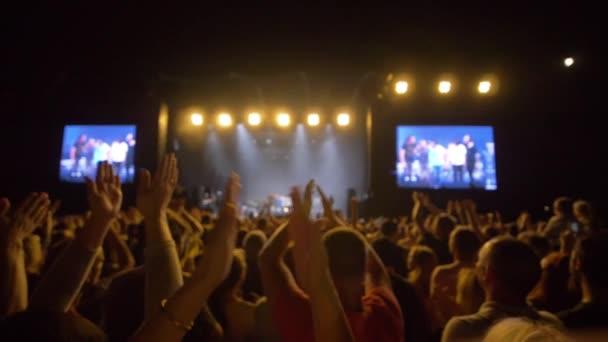 rocková hudební událost, dav fanoušků tleskat ruce a vychutnat si živý festival v jasně osvětlených scénách ve zpomaleném filmu