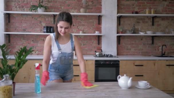 Hausreinigung, schöne Haushälterin in Gummihandschuhen zum Putzen reibt staubige Möbel mit Spülmittel