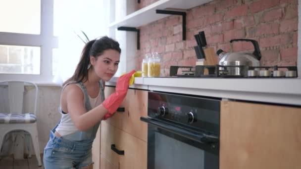 portrét šťastné ženy v domácnosti v gumových rukavicích při všeobecném čištění kuchyně a domácí práce