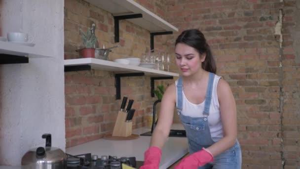 Porträt einer lächelnden Hausfrau in Gummihandschuhen bei der allgemeinen Reinigung von Küche und Haushalt