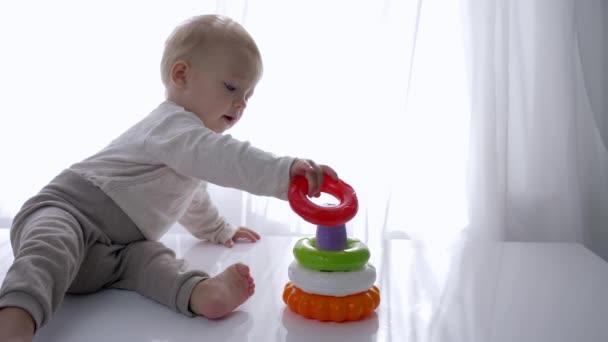 baby development, roztomilý chlapeček se hraje se vzdělávací hračkou pyramida v světlé místnosti