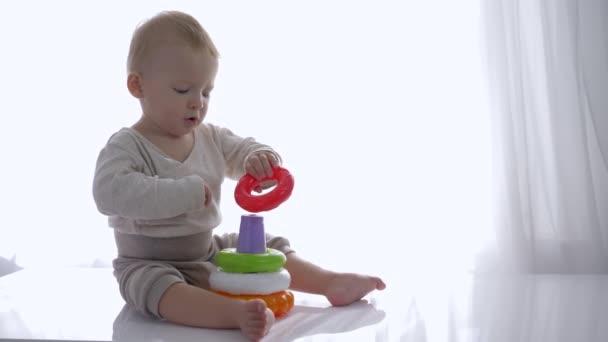 zvědavý batole chlapec hrál s vzdělávací hračka věž v světlé místnosti
