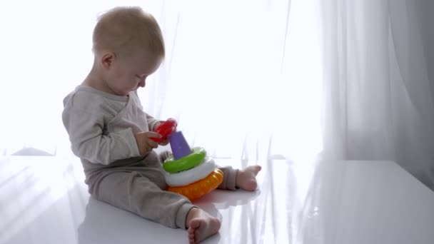 dítě vzdělávací, kojenecký chlapec se hraje s věží hraček v světlé místnosti