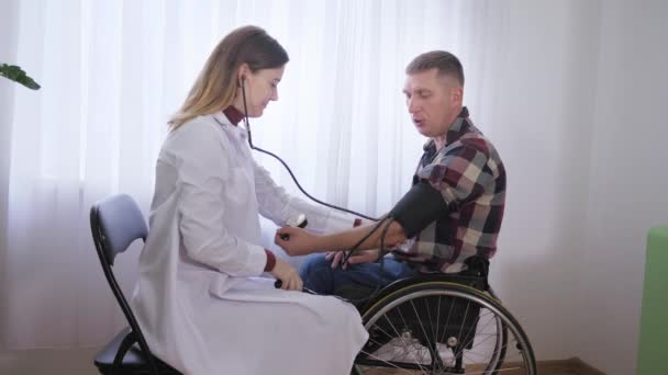 Gesundheit eines behinderten Menschen, der im Rollstuhl sitzt, wird von einem Arzt untersucht, misst während einer ärztlichen Untersuchung den Druck mit einem Gerät