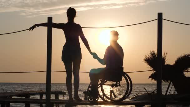 Mädchen mit Freund behindert Händchen halten auf Pier stehen und Blick auf Sonnenuntergang