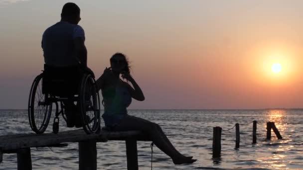 lachendes Mädchen, das auf der Seebrücke sitzt und mit Behinderten im Rollstuhl vor Sonnenuntergang und Meer spricht